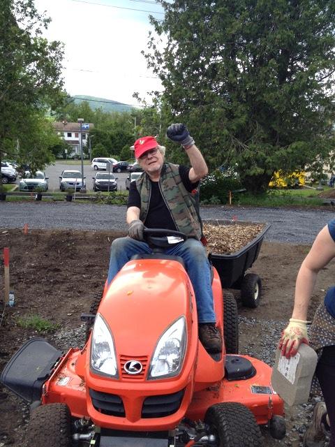 Henri transportant du paillis lors de l'aménagement devant la grange.